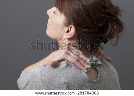 50s woman leaning her head for head and backbone relaxation - stock photo