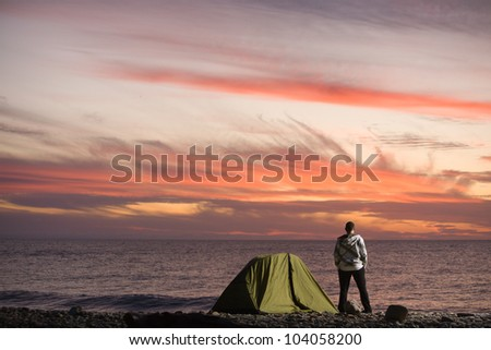 30s years old man near the sea standing and looking at sunset - stock photo