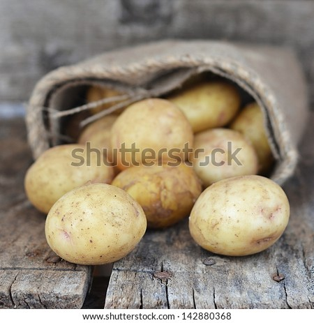 Sack fresh organic potatoes on a wooden table - stock photo