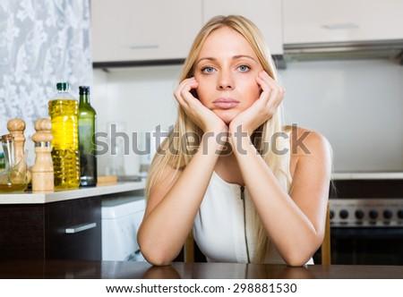 sad  blonde  woman sitting  at  kitchen - stock photo
