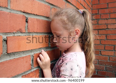 sad child with a brick wall - stock photo