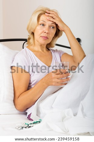 Sad female pensioner  in bed with pills and glass of water - stock photo