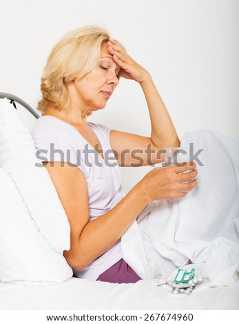 Sad female pensioner laying in bed with pills and glass of water - stock photo
