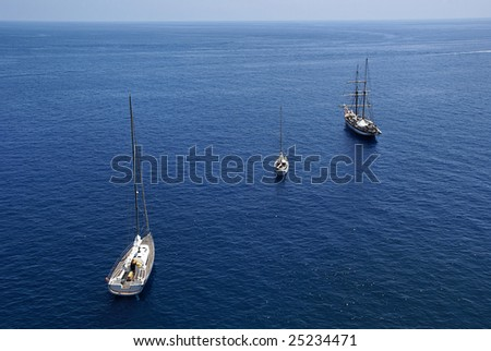 3 sail boats in blue water, forming a diagonal. - stock photo