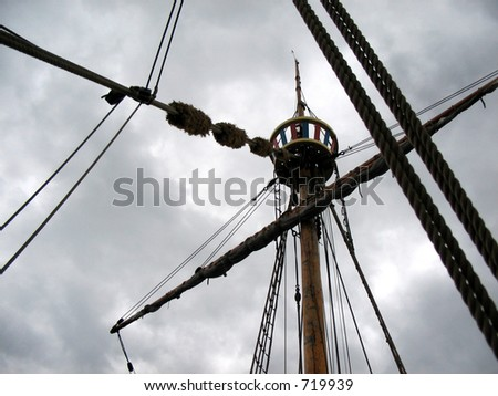 Sailing ship's furled canvas sails and complicated rope - stock photo