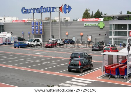 SAINT-LO, FRANCE - JULI 23: Half-empty parking of a Carrefour hypermarket, a French multinational retailer, and one of the largest hypermarket chains in the world on Juli 23, 2014 in Normandy, France - stock photo