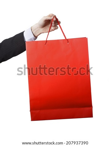 sales Man hand carrying and showing a Red Sale Shopping Bag isolated on white background