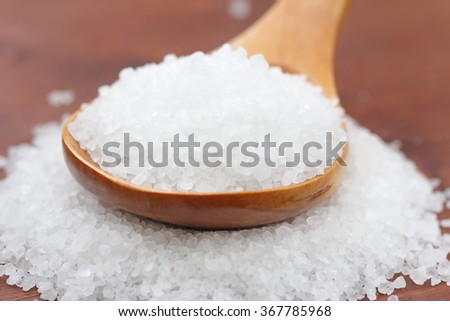Salt in wooden spoon on wooden background