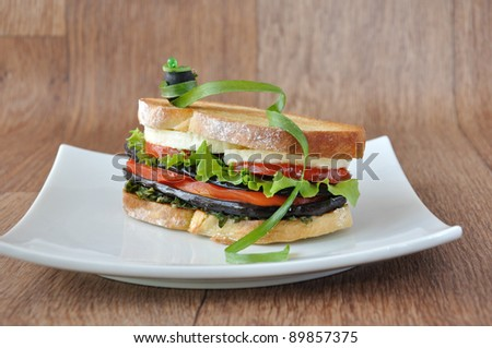 Sandwich with eggplant, tomatoes, peppers and cheese