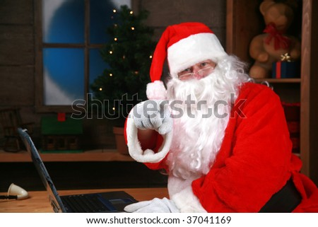 """santa claus"" points at ""you the viewer"" while in his workshop in the ""north pole"" - stock photo"