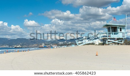 SANTA MONICA, USA - OCTOBER 6: Santa Monica Beach lifesavers lookouts dark cloud formation overhead and pier and hills around Los Angeles  in distance October 6,2015, Santa Monica USA