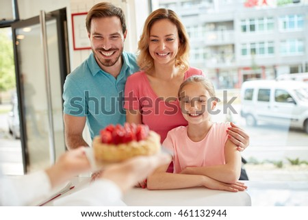 Satisfied family with girl look at strawberry cake in bakery