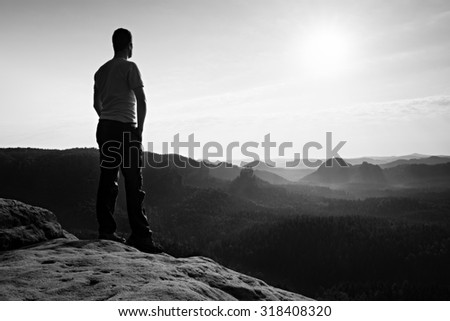 Satisfy hiker in grey shirt and dark trousers. Tall man on the peak of sandstone cliff watching down to landscape. Black and white photo.
