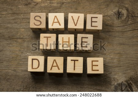 Save the Date text on a wooden blocks on a wooden background - stock photo