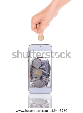 saving coins with mobile phone - stock photo