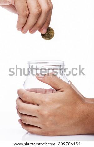 Saving concept-hand putting a coin into glass bottle