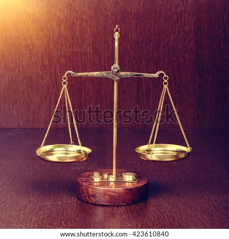 scales on wooden table, law concept - stock photo