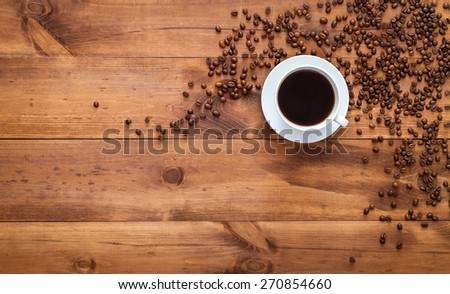 Scattered grains of coffee on the table top view. Grains with  Hot Brewed Coffee in mug.  Coffee cup and saucer on a wooden table. For registration booklets and advertising of coffee. - stock photo