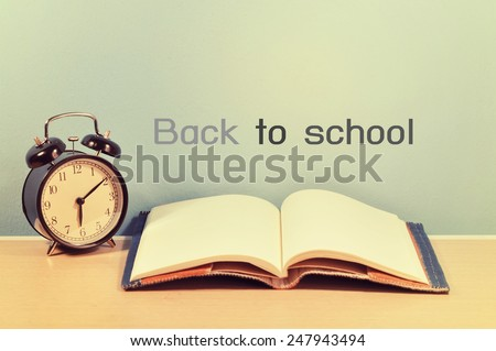 "school books and clock with ""back to school"" on background - stock photo"