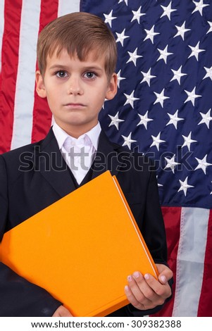 schoolboy is holding an orange book against USA flag