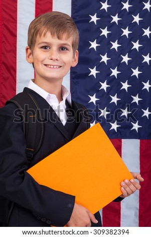 schoolboy is holding an orange book against USA flag - stock photo