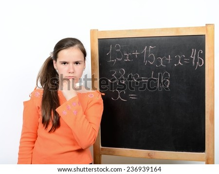 Schoolgirl teen thought about solving mathematical equations on the a school blackboard