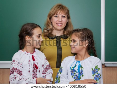 Schoolgirls in embroidered shirts and teacher in the classroom at the blackboard - stock photo