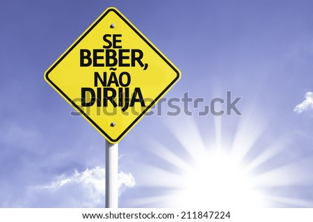 """Se Beber, N�£o Dirija"" (In portuguese - Don't Drink and Drive) road sign with sun background  - stock photo"
