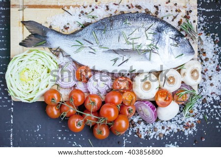 Sea fish with fragrant herbs, fresh vegetables, sea coarse salt and spices. - stock photo