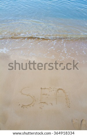 """Sea"" written in the sand on the beach - stock photo"