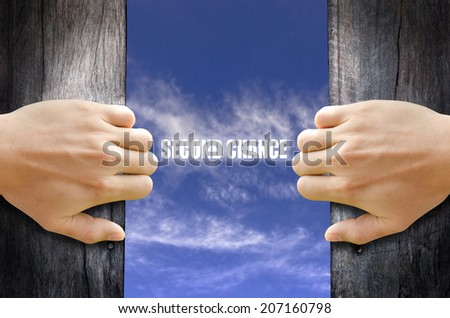 """""""Second Chance"""" text in the sky behind 2 hands opening the wooden door. - stock photo"""