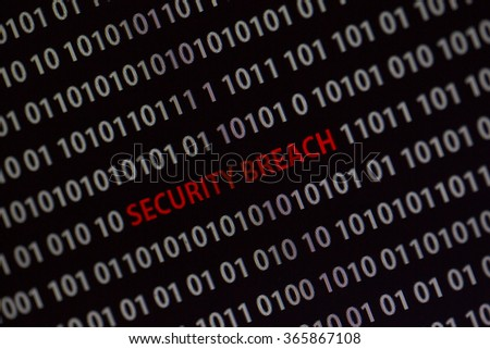 'Security breach' text in the middle of the computer screen surrounded by numbers zero and one. Image is taken in a small angle.