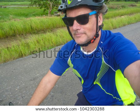 'Selfie' of a male cyclist in a blue shirt riding through the countryside of eastern Thailand
