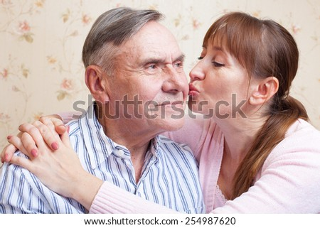 Senior father. Family adult daughter kissing senior father. Elderly man with her caregiver at home. - stock photo
