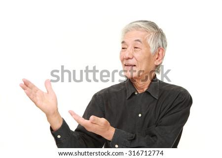 senior Japanese man presenting and showing something  - stock photo