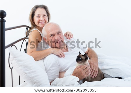 Senior  man and   woman resting on   bed in   embrace.