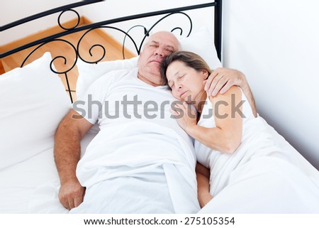 Senior  man and   woman sleeping on   bed in   embrace.