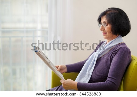 Senior woman reading news paper on sofa at home