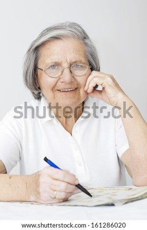 Senior woman sitting at table and solving crossword puzzle. - stock photo