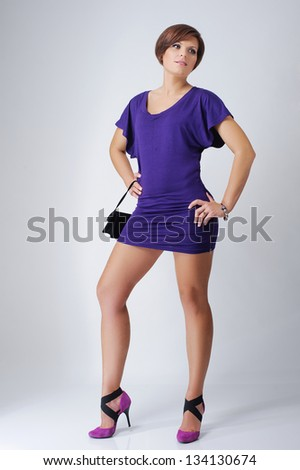 Sensual, beautiful woman in a purple dress dancing and bursting with joy/ Woman's long legs and fashionable styling on a light background