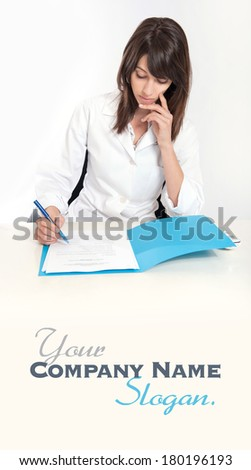 Serious young woman in a lab coat sitting at the desk  with an open folder