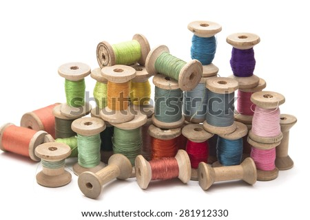 set of colored thread for sewing on wooden spools, vintage, white background - stock photo