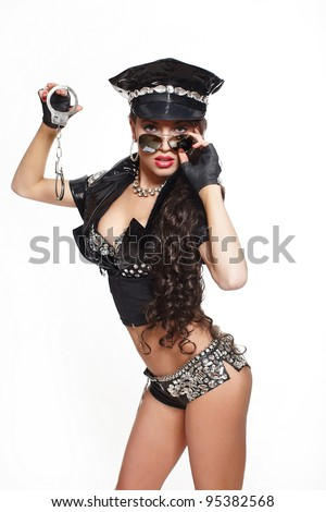 sexy beautiful  brunette semi nude police woman with long curly hair with handcuffs with glasses with bright makeup and red lips isolated on white - stock photo