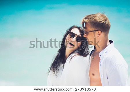 sexy couple young beautiful girl and the man in sunglasses and white clothes on their honeymoon in Cyprus on the beach