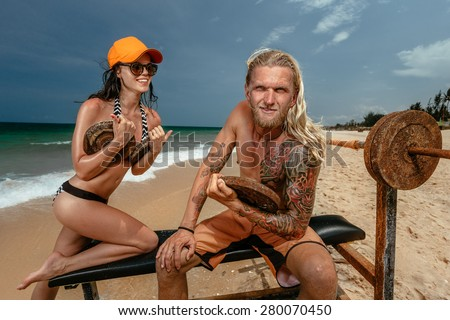 Sexy woman and man doing weight lifting on sea beach - stock photo