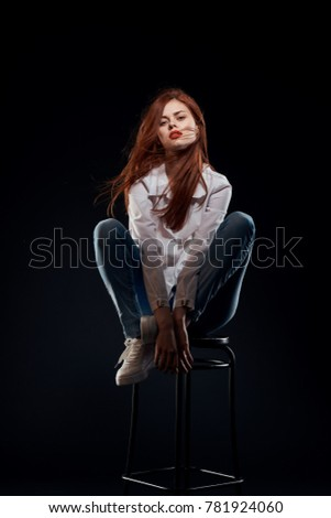 sexy woman with an unbuttoned shirt on a chair sits on a black background