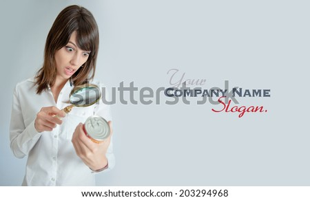 Shocked young   woman inspecting a can�¢??s nutrition label with a magnifying glass  - stock photo