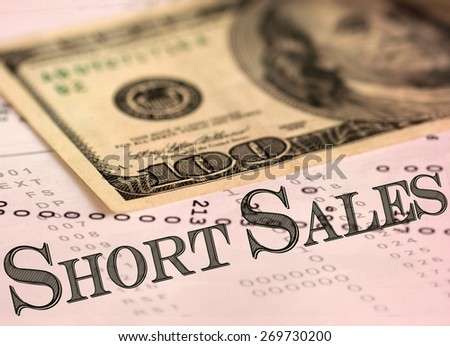 """Short sales"" wording with blurred hundred dollar bill in the background.  - stock photo"