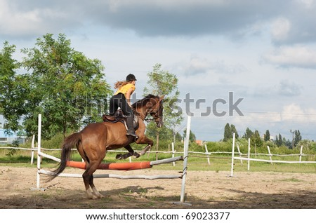 show jumping.girl riding horse and jumping