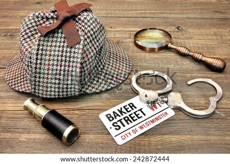 sign Baker Street City of Westminster and Real Handcuffs on Grunge Wooden Table - stock photo